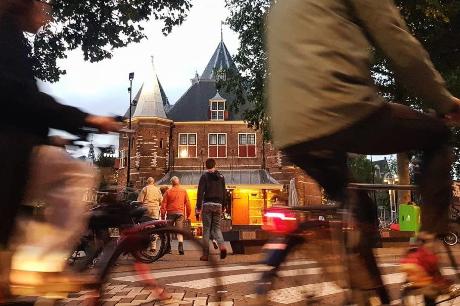 Cycling in busy city center of Amsterdam at de Waag. Photo by Tom van der Leij.