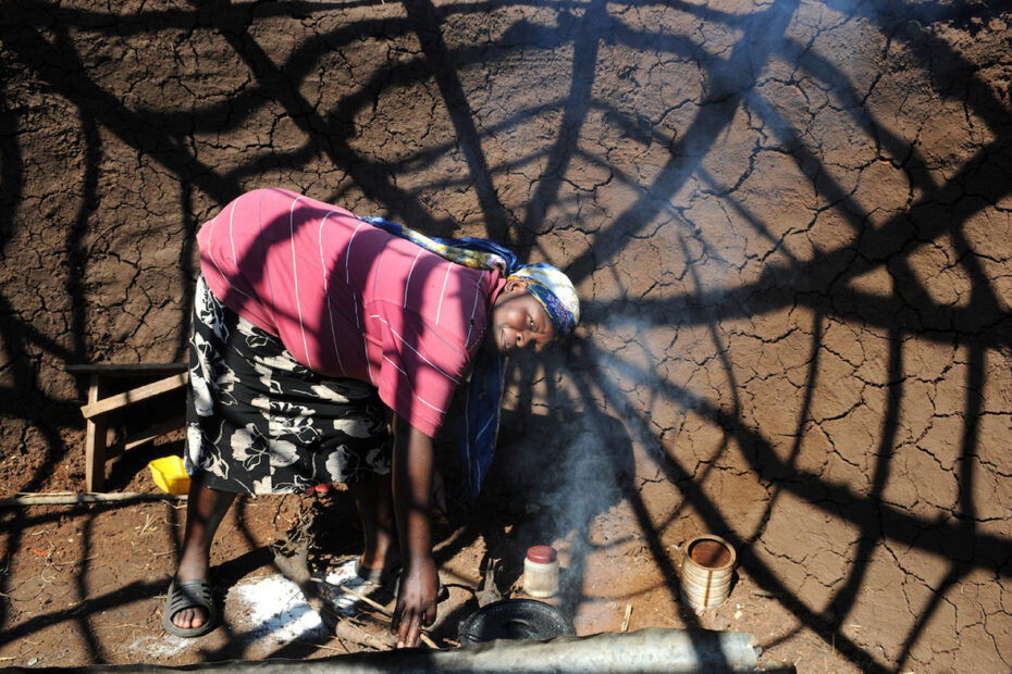 A woman is cooking in front of her unfinished home in South Africa by Amsterdam photographer Tom van der Leij