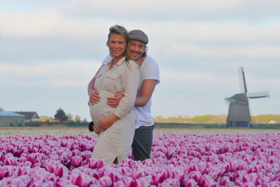 Couple in tulip fields celebrating pregnancy. Maternity photoshoot. Photo by Amsterdam photographer Tom van der Leij