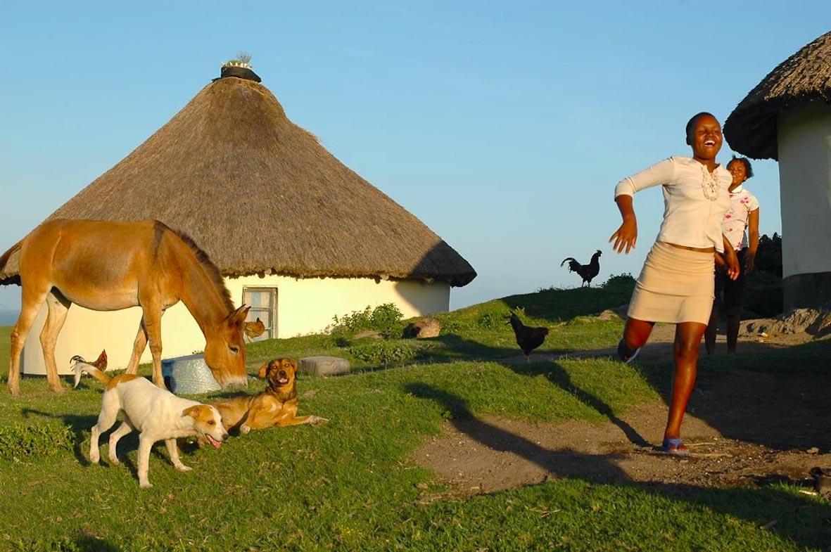 Woman running on a farm in South Africa, Wild Coast, Transkei by Amsterdam photographer Tom van der Leij
