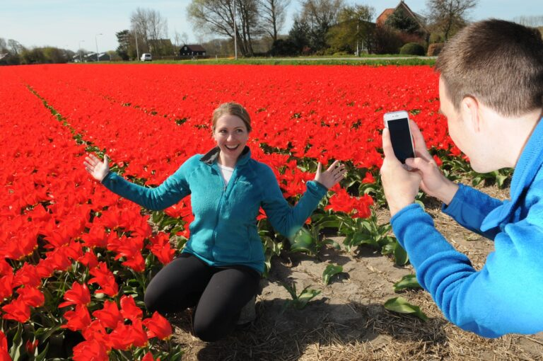 Couple taking photos of eachother in tulip fields in Holland