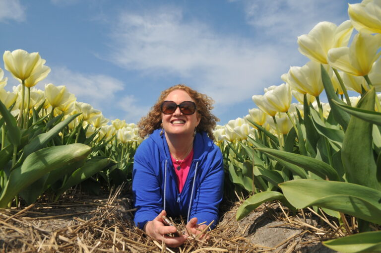 Woman in the middle of tulips in Holland by Amsterdam photographer Tom van der Leij