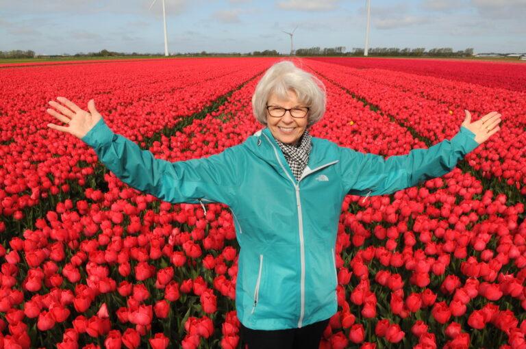 Woman in Dutch red tulip fields by Amsterdam photographer Tom van der Leij