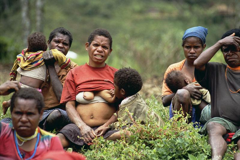 Papua women standing in bush by Tom van der Leij